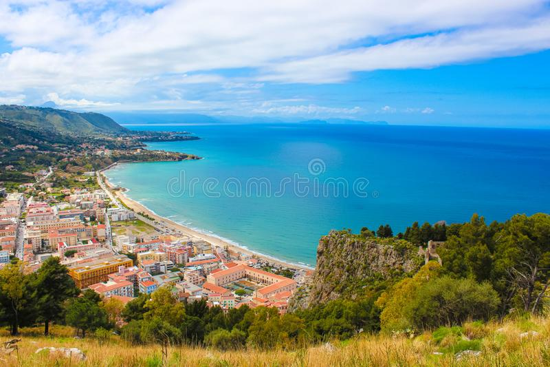 Stunning view over the bay on Tyrrhenian coast by city Cefalu, Sicily, Italy. On the adjacent rocks overlooking blue sea. There are medieaval castle ruins Rocca royalty free stock photo