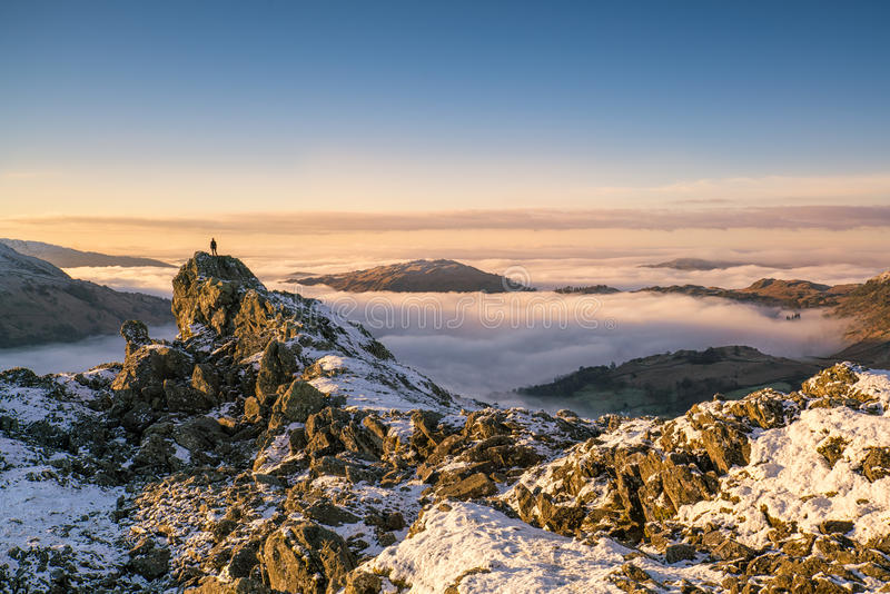 Stunning view over an inversion in Grasmere, Lake District. A solitary figure stands atop the iconic Lion & Lamb snow covered rocky pinnacle on the summit of stock photo