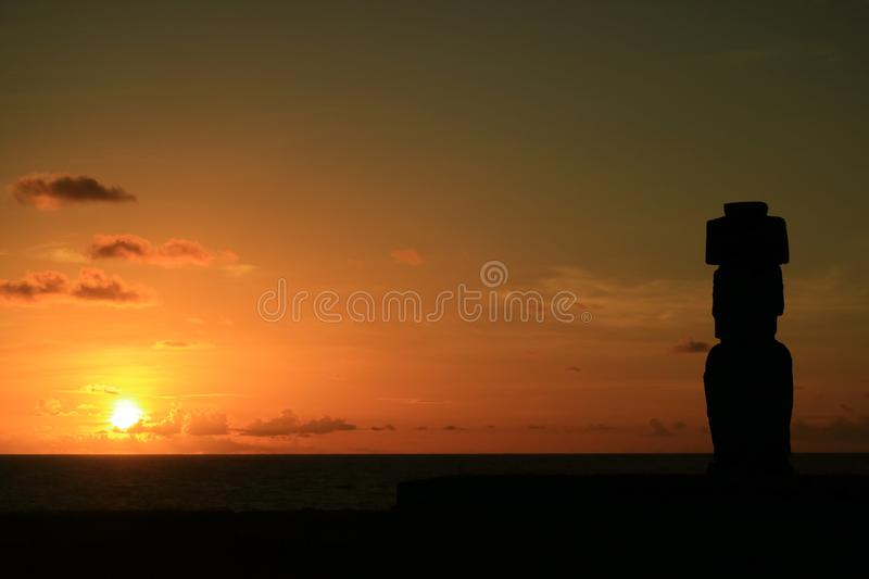 Stunning view of the sun setting over Pacific ocean with Moai`s silhouette at Ahu Tahai, Easter Island royalty free stock image