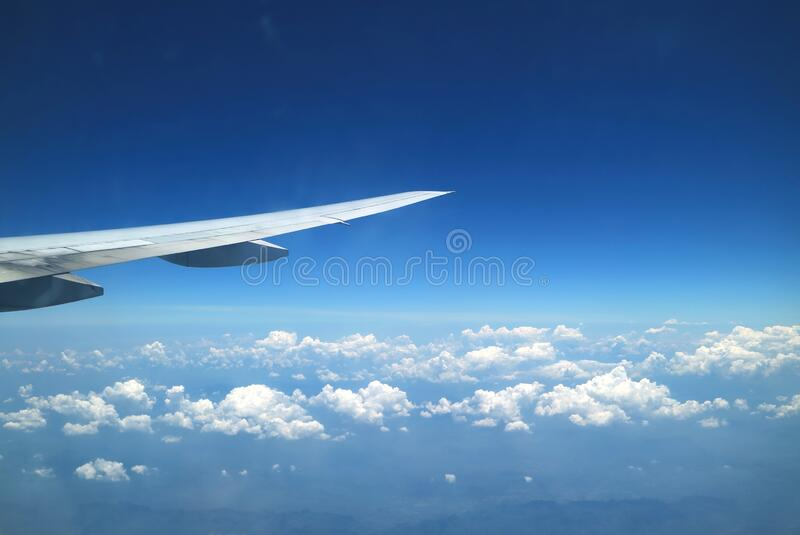 Stunning view of vivid blue sky and pure white clouds with airplane wing seen from plane window during flight stock images
