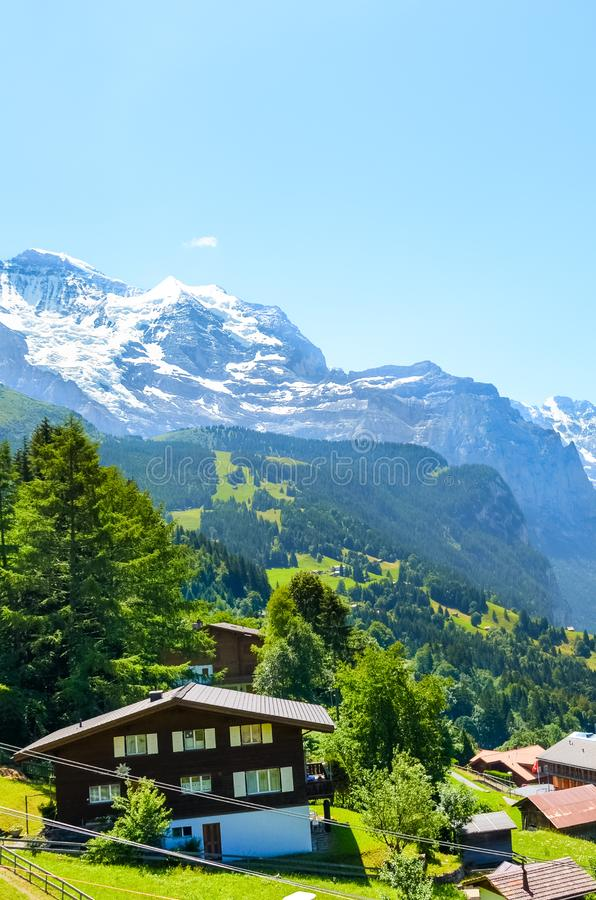 Stunning village Wengen in Swiss Alps. Mountain ridges with snow on top in background. Switzerland summer. Alpine landscape. stock image