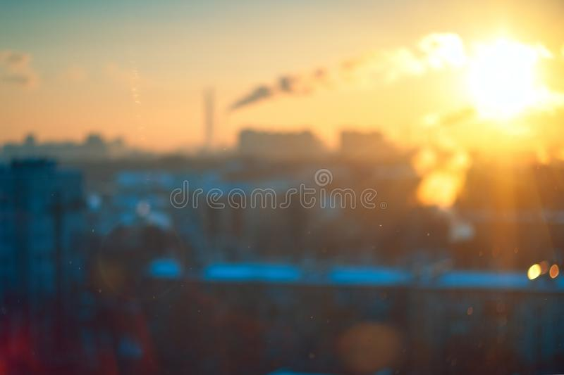 Stunning vintage amber blue sunset light with blurred industrial cityscape skyline bokeh background through frozen window glass. stock photography