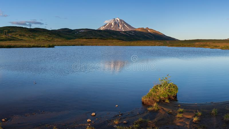 Stunning volcanic landscape at sunset: reflection of mountains in alpine lake stock image