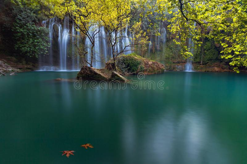 Two autumn leaves in an emerald lake with stunning waterfalls in deep green forest in Kursunlu Natural Park, Antalya, Turkey. Stunning waterfalls with small royalty free stock photos