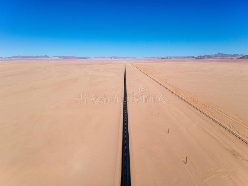 Stunning wide angle aerial drone view of the B4 desert road and a train line between Lüderitz and Keetmanshoop royalty free stock photo
