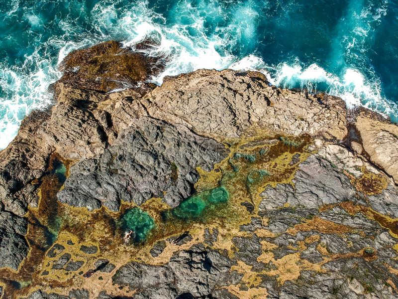 Stunning wide angle aerial drone view of the Mermaid Rock Pools and ocean waves at Matapouri Bay near Whangarei on the North Islan royalty free stock image