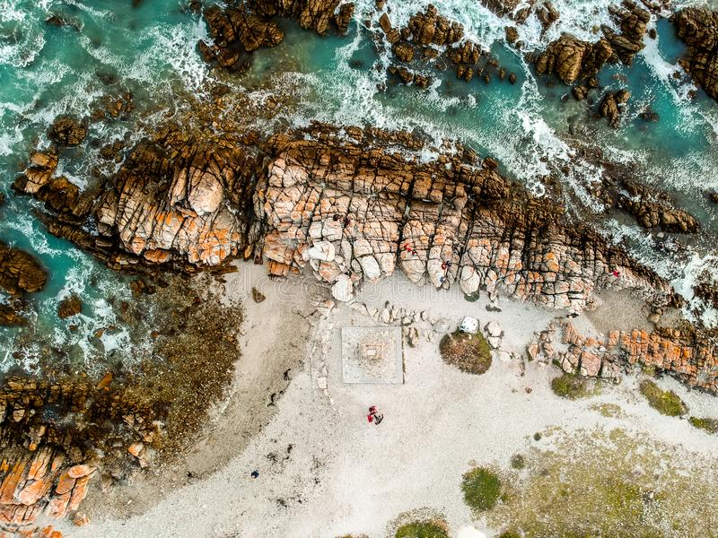 Stunning wide angle aerial drone view of rocks and breaking waves at Cape Agulhas royalty free stock photo