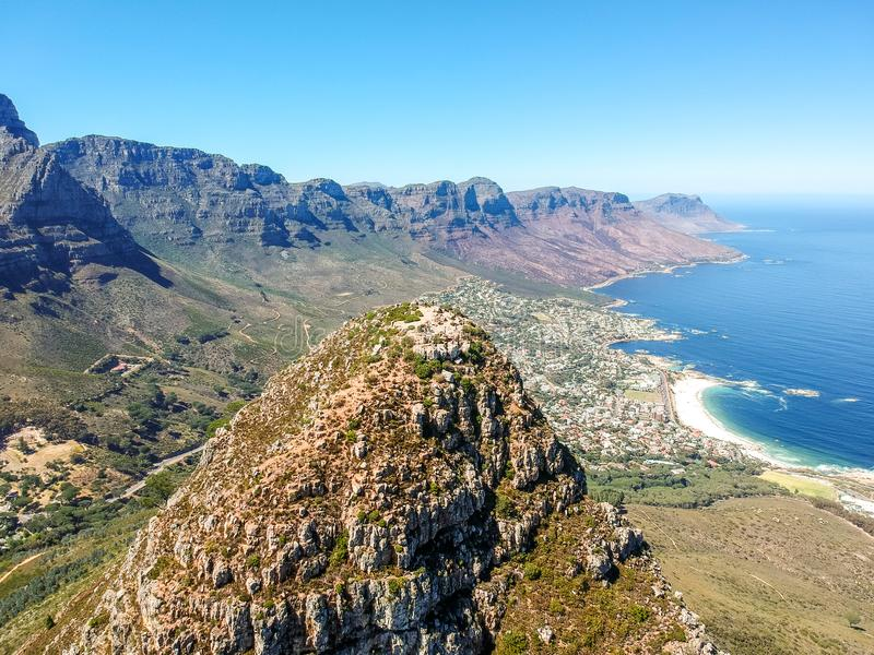 Stunning wide angle aerial drone view of the summit of Lion`s Head mountain and the suburb of Camps Bay with the Twelve Apostles m royalty free stock images