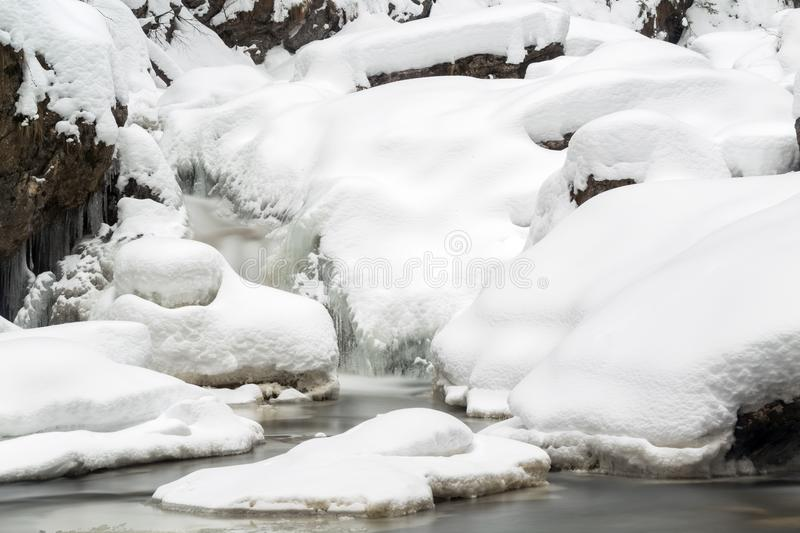 Stunning winter landscape, stones on wintry river covered snow a. Nd small waterfall, Europe travel, Carpathian, Romania stock images
