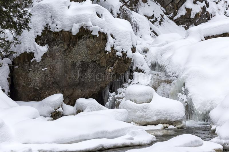 Stunning winter landscape, stones on wintry river covered snow a. Nd small waterfall, Europe travel, Carpathian, Romania stock image