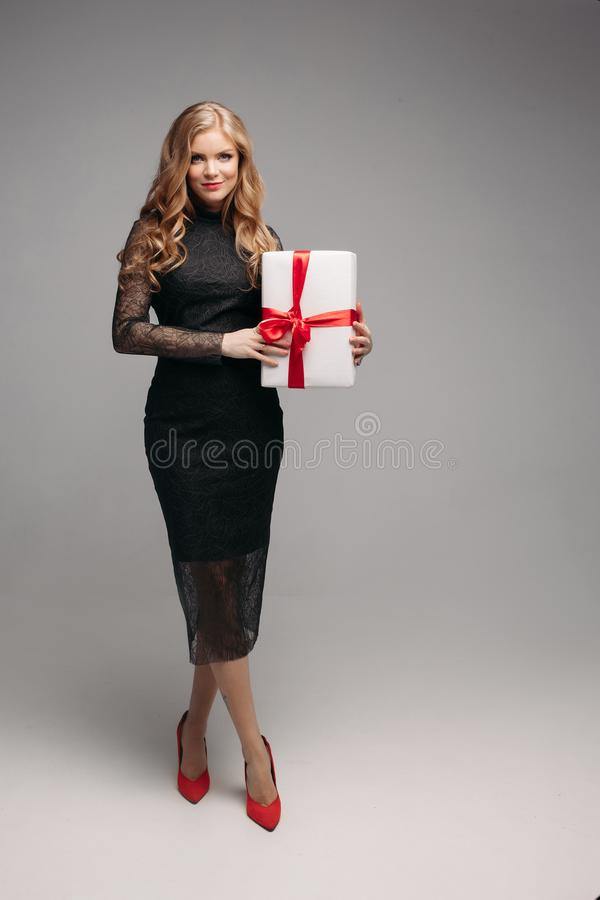 Stunning woman in elegant black dress with Christmas gift. Studio portrait of attractive blonde woman with wavy hair wearing elegant laced black dress holding stock photography