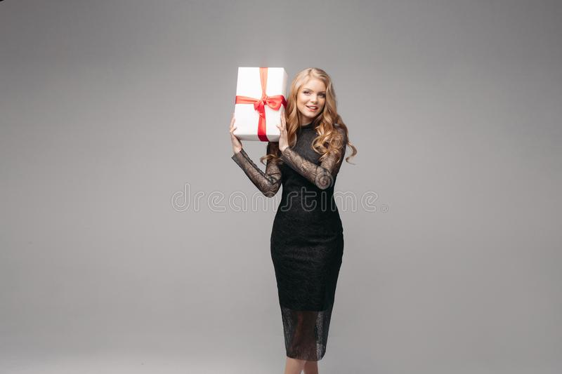 Stunning woman in elegant black dress with Christmas gift. Studio portrait of attractive blonde woman with wavy hair wearing elegant laced black dress holding stock photo