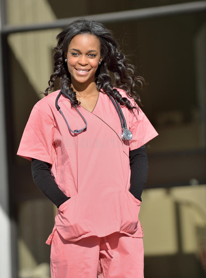 Stunning young African American female healthcare worker. Stunning young African-American female healthcare professional in Pink scrubs standing in front of an stock photo