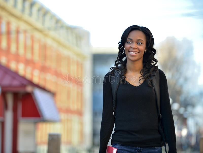 Stunning young African American female student on campus. Stunning young African American female student walking with backpack and boot - outside on campus royalty free stock photos