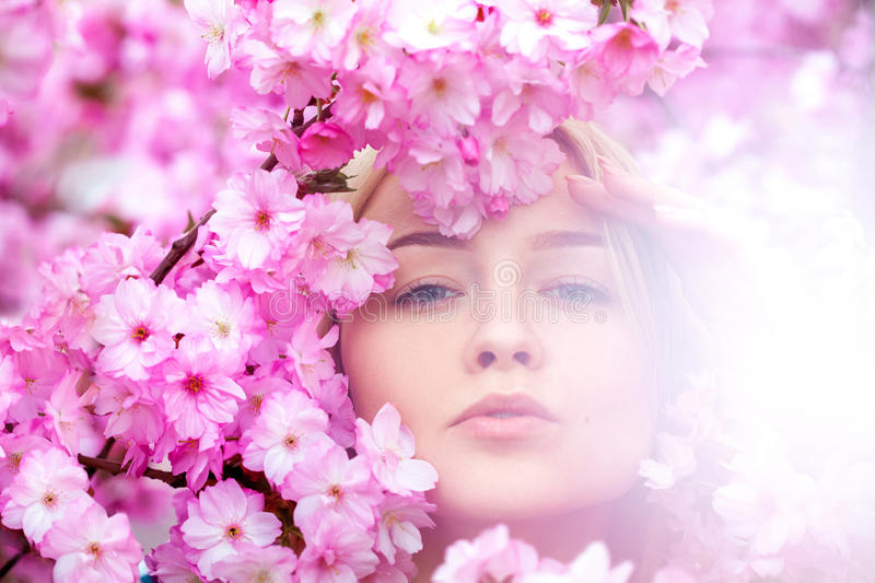 Stunning young blonde in bright pink flowers. Spring time royalty free stock photo