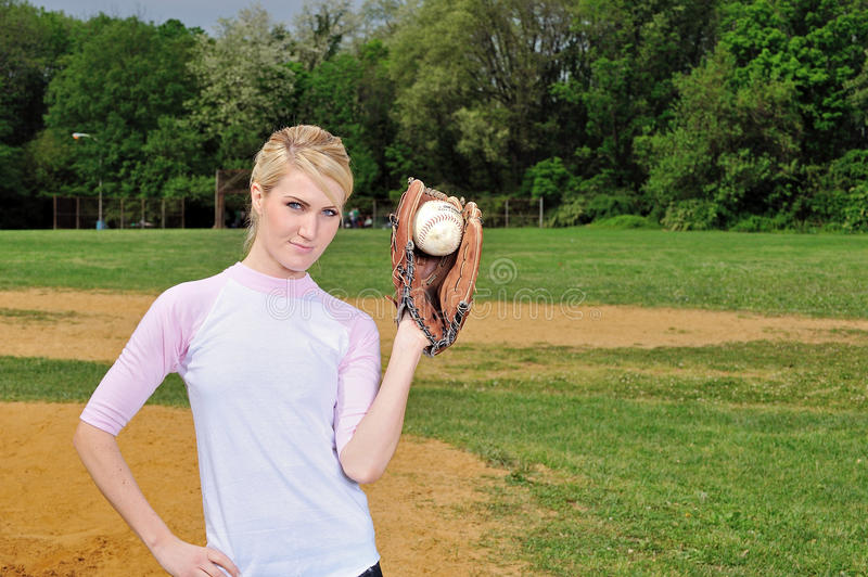 Stunning young blonde female softball player. In pink and white baseball jersey shirt - holding softball in glove up royalty free stock photo