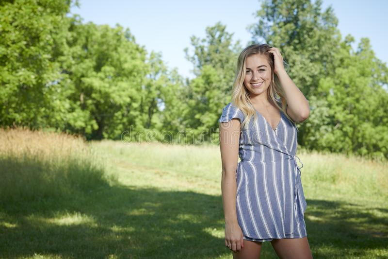 Beautiful young blonde woman poses in striped dress - summer fashion royalty free stock images