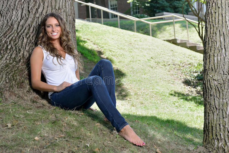 Stunning young Hispanic woman in jeans and tank top. Stunning young Hispanic woman in white tank top and blue jeans - casual fashion - posing in park next to stock photography