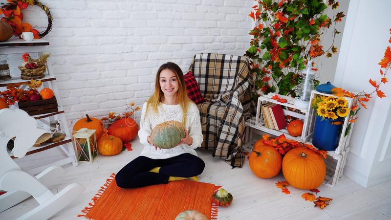 Cute Girl Posing With Pumpkins, Smiling and Sitting on Floor in Bright Room on stock photo