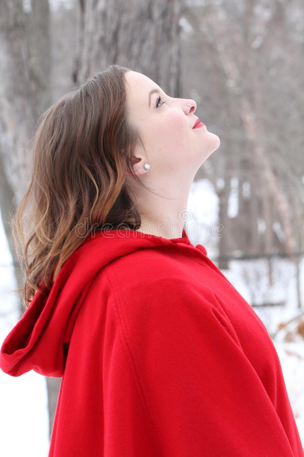 Beautiful long haired woman in red cape outdoors in winter looking up royalty free stock photos