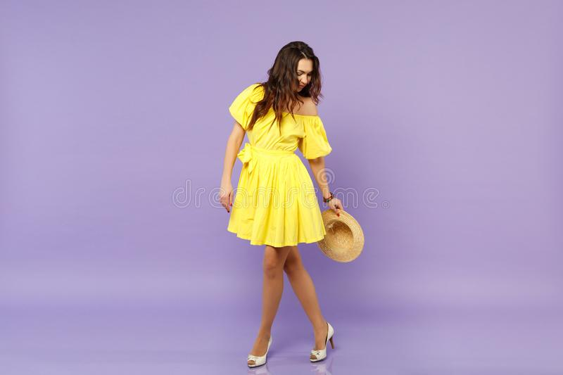 Stunning young woman in yellow dress holding summer hat, standing, looking down isolated on pastel violet wall stock photos