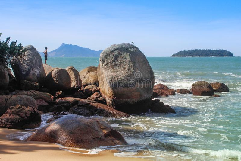 Stunningly beautiful beach with turquoise water, stones and rocks. A man stands on a stone. Landscape with the beach of Brazil on stock photo
