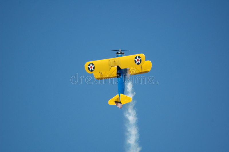 Stunt biplane 3. Stunt biplane against blue sky with smoke royalty free stock images