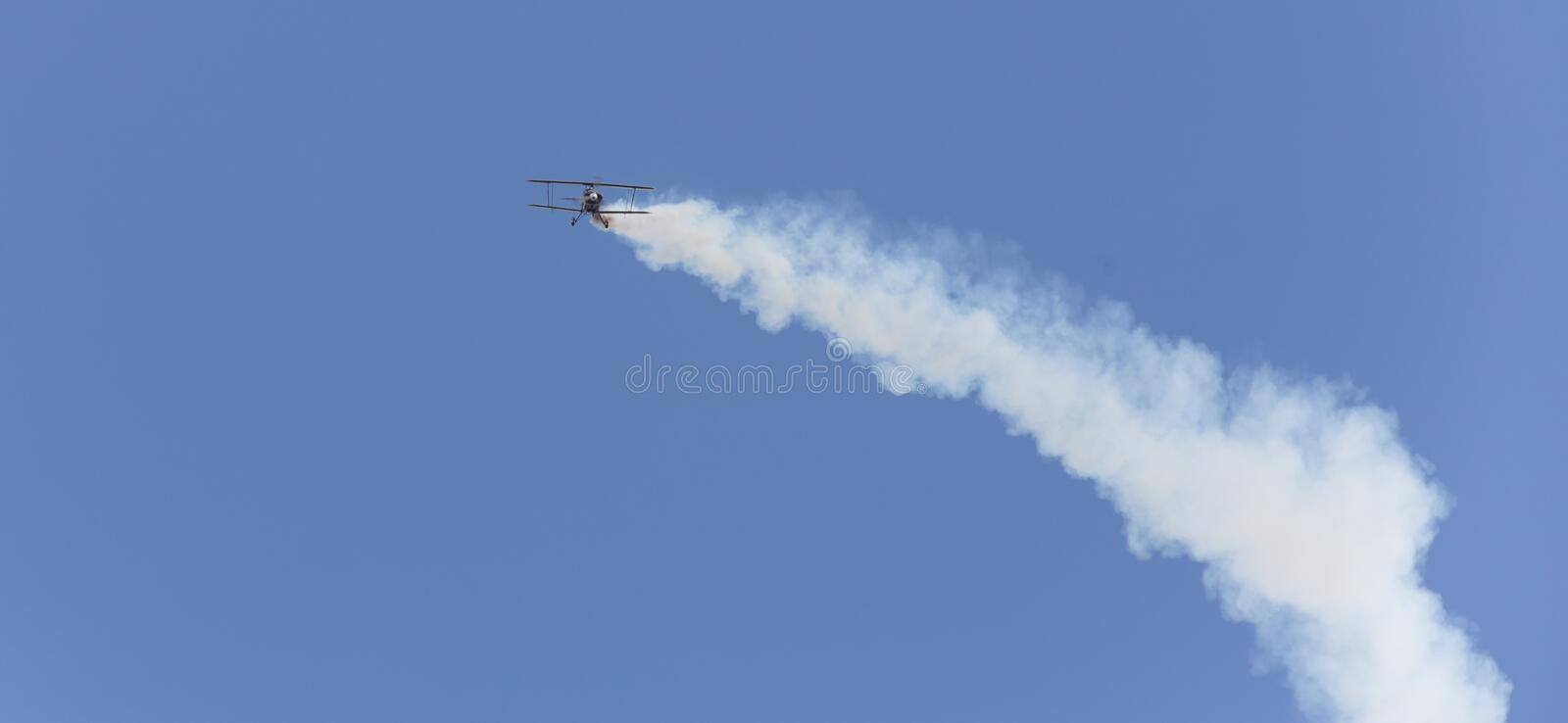 Stunt flyer airplane in the sky. A stunt flyer airplane in the sky royalty free stock photo