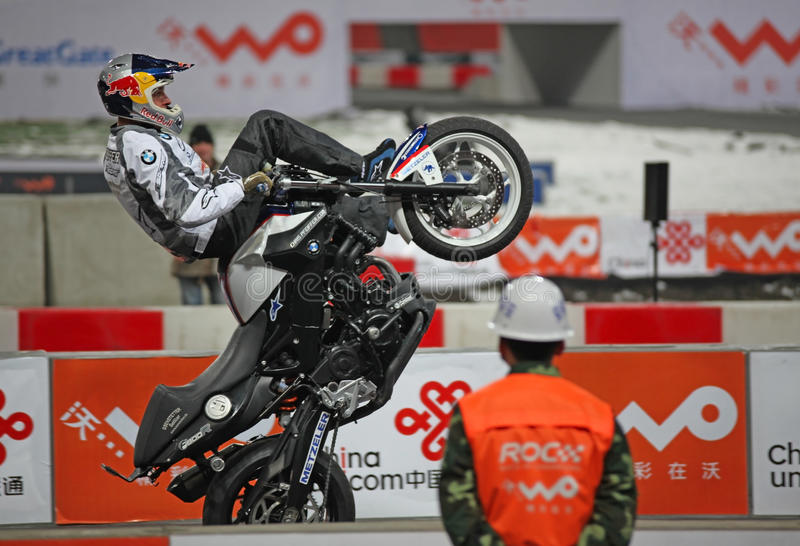 Stunt rider. Chris Pfeiffer entertains at Beijing National Stadium (The Bird's nest) while a security guard is watching his performance, during the Race stock photos