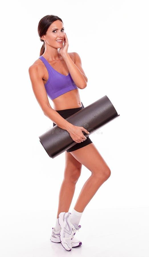 Stuoia castana sorridente sana di yoga della tenuta fotografia stock libera da diritti