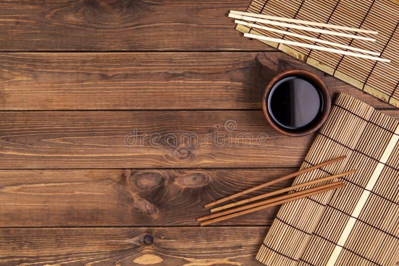 Stuoia per i sushi ed i bastoncini su fondo di legno fotografie stock libere da diritti