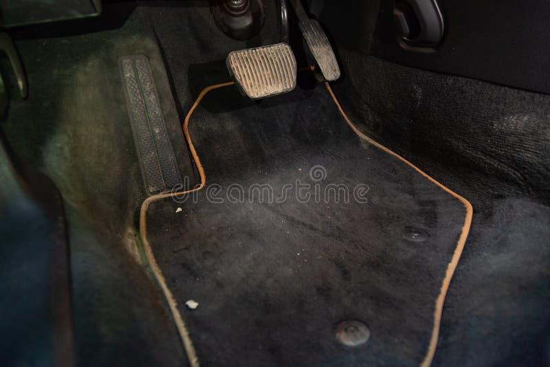 Stuoie sporche del pavimento dell'automobile di tappeto nero con i pedali ed i freni di gas nell'officina per il veicolo dettagli fotografie stock