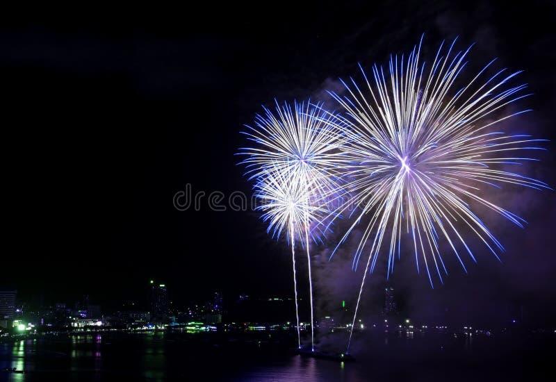 Stup?faction des feux d'artifice bleus et blancs ?clatant dans le ciel nocturne au-dessus de la baie photos stock