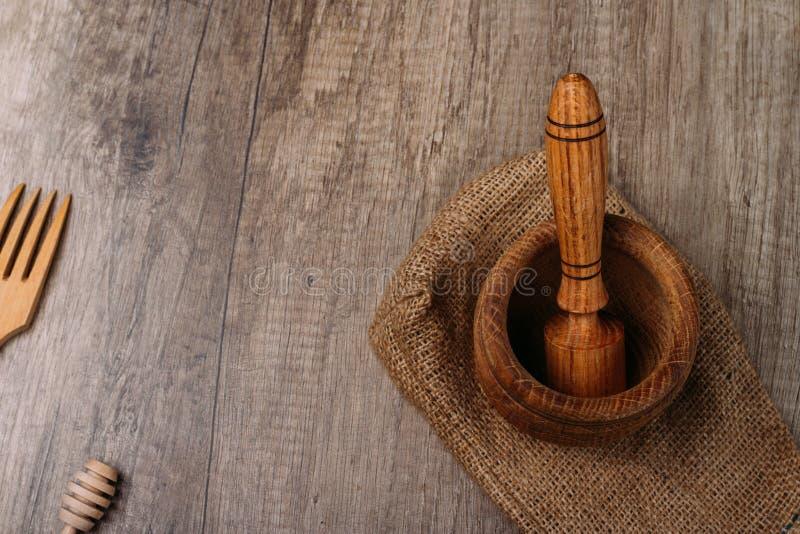 stupa и пестик на мешковине на таблице деревни kitchenware толкотня вилка и ручка для меда ручной эко-друг рекламации специи стоковые фото