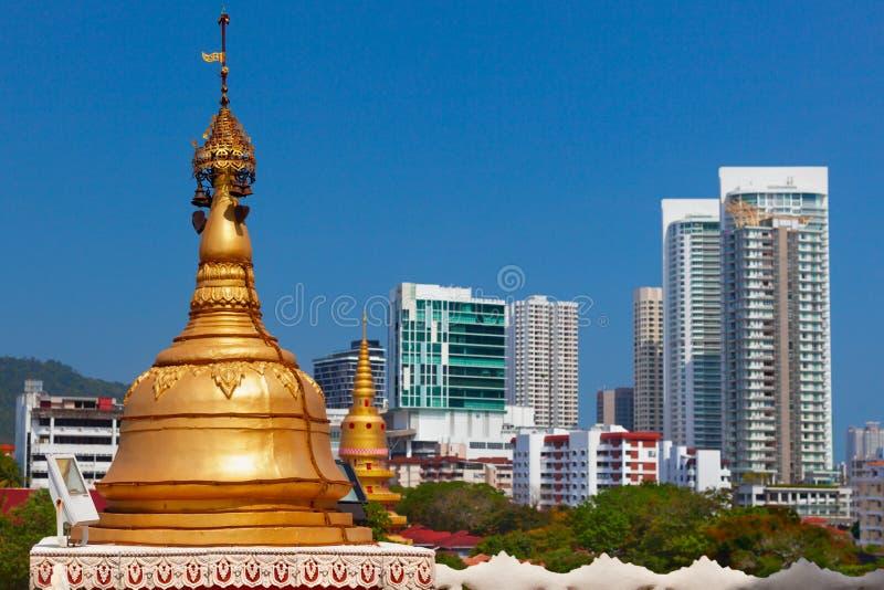 Stupa budista dourado no fundo moderno das construções da cidade fotografia de stock royalty free