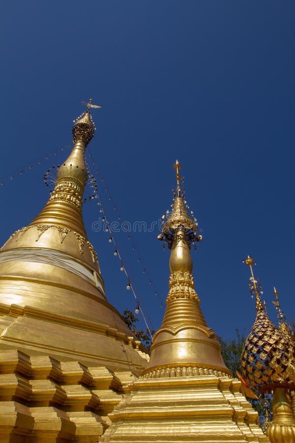 Stupa, chedi e pagoda dorati in tempio buddista in Tailandia con il fondo del cielo blu fotografia stock libera da diritti