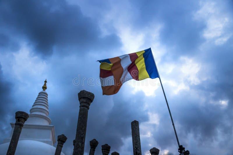 A Stupa, Clouds and a flag, Anuradhapura, Sri Lanka. Stormy weather over a stupa in Sri Lanka stock images