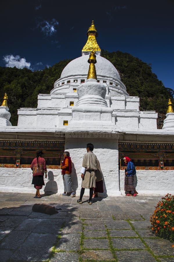 Stupa de Chorten Kora, pessoa que rola as rodas de oração, distrito de Trashiyangtse, Butão oriental fotografia de stock