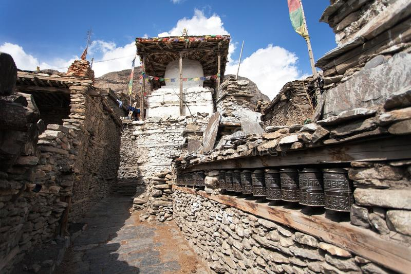 Stupa and prayer wheels wall in Manang villlage. One of the best villages in round Annapurna circuit trekking trail route, Nepal royalty free stock image