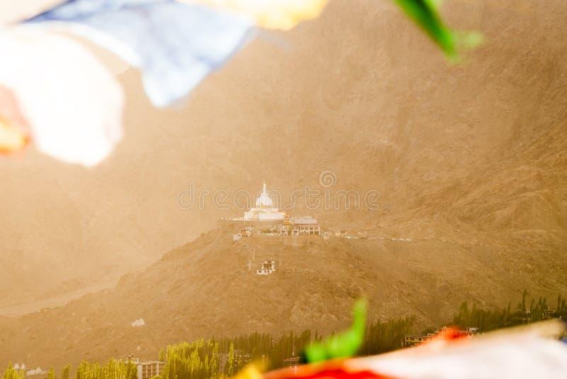 Stupa Shanti μέσω των σημαιών προσευχής στο χρόνο ηλιοβασιλέματος με το φως του ήλιου στοκ φωτογραφίες με δικαίωμα ελεύθερης χρήσης