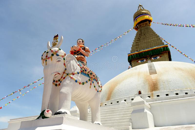 Stupa and statue, Kathmandu, Nepal. Statue of person riding elephant in front of stupa in Kathmandu, Nepal against blue skies royalty free stock photo
