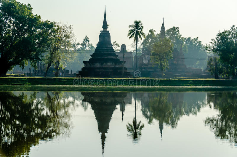 Stupa Temple in Thailand with water reflection on Lake. Simetric reflection of the famous Sukhotai Stupa in Thailand stock photos
