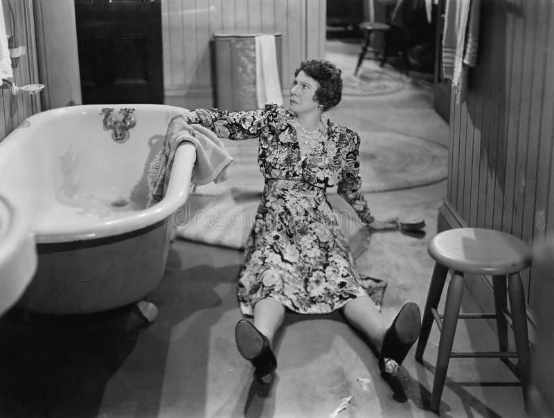 Stupad kvinna på golv bredvid badkaret (alla visade personer inte är längre uppehälle, och inget gods finns Leverantörgarantier d arkivbilder