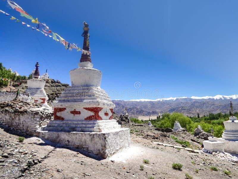 Stupas、祷告旗子和山脉 免版税库存图片