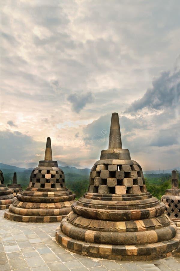Stupas antichi in tempio buddista di Borobudur contro il cielo drammatico fotografie stock
