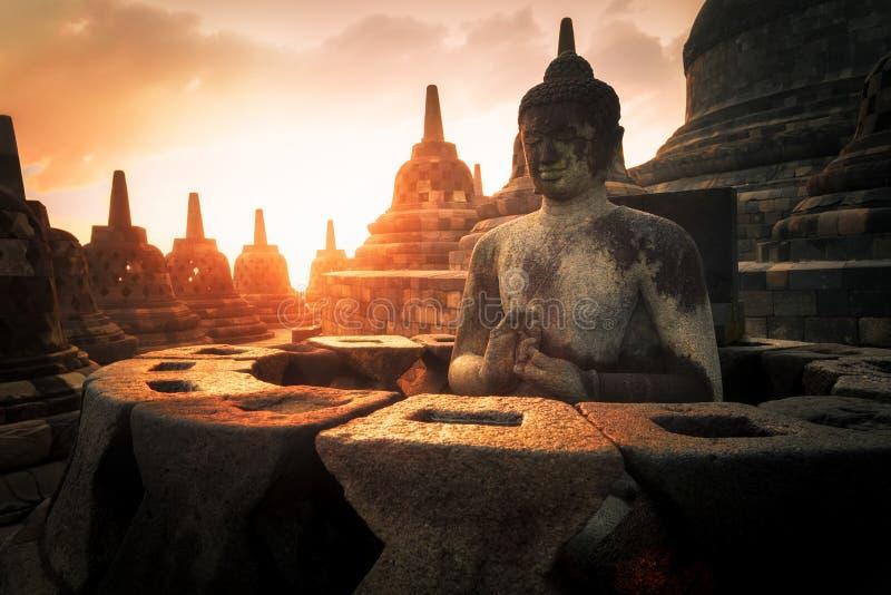 Stupas della statua e della pietra di Buddha contro il sole brillante Tempiale di Borobudur l'indonesia immagine stock libera da diritti