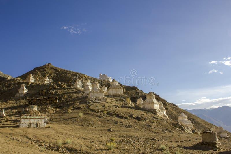 Stupas tibetanos brancos antigos dos templos budistas na inclinação de um monte do deserto contra o vale do céu azul e da montanh imagens de stock royalty free