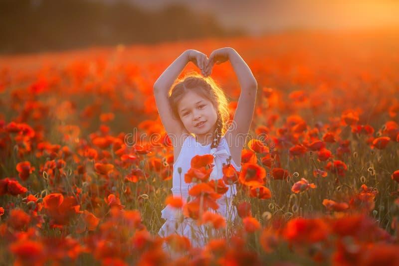 Stupendo vicino sul ritratto di giovane ragazza romantica sveglia adorabile con il fiore del papavero a disposizione che posa sul fotografia stock