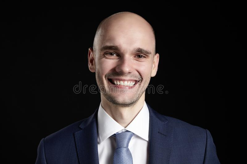 Stupid Smiling Man. Studio portrait of young goofy man against black background. Funny face stock image