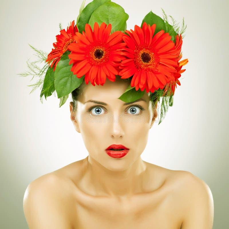 Stupito con il gerbera rosso fiorisce sulla sua testa immagini stock